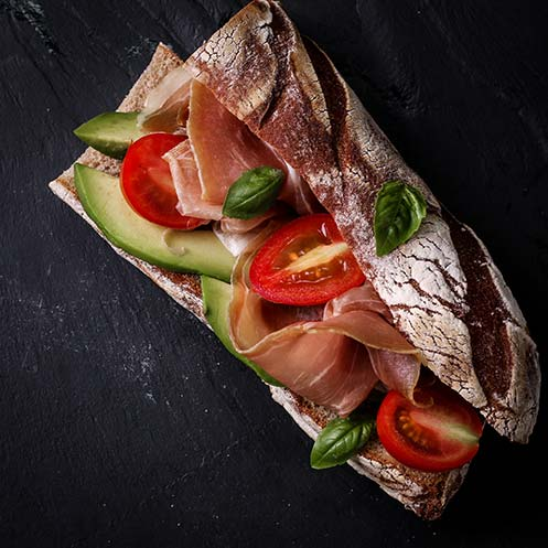 Prosciutto sandwich with avocado and basil