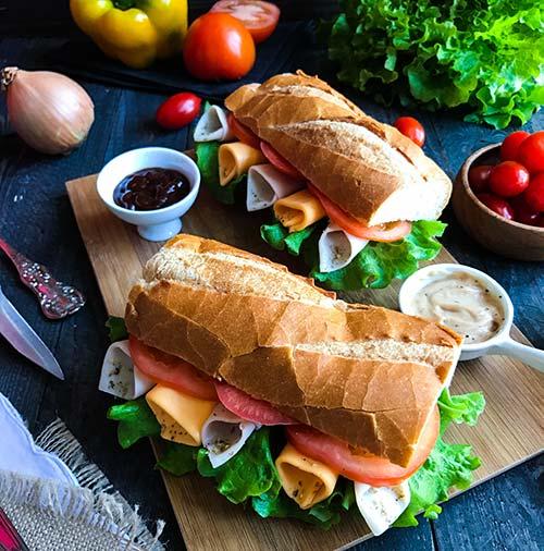 Two turkey sandwiches on a cutting board